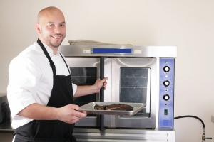 Happy chef taking his freshly baked rib-eye steak