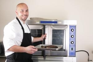 Happy chef taking his freshly baked rib-eye steak