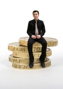 business man sitting on coins