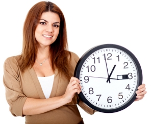 Woman holding a clock and smiling - isolated over a white background