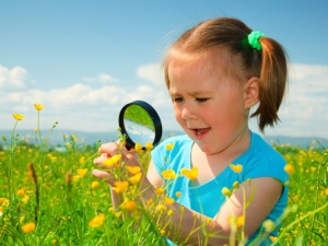 Little girl examining flowers using magnifier